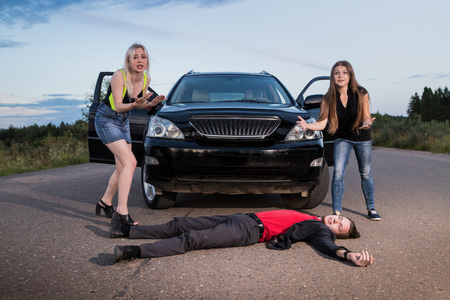 Two girls hitting male drunk pedestrian on the road in the summer evening. Photoshoot