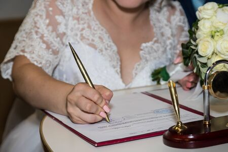 Kirov, Russia - July 27, 2018: Bride and groom signing marriage wedding certificate at registry office