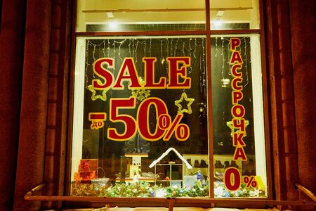 Kirov, Russia - December 28, 2018: Show window of shop with text about sale at discount in russian language at night