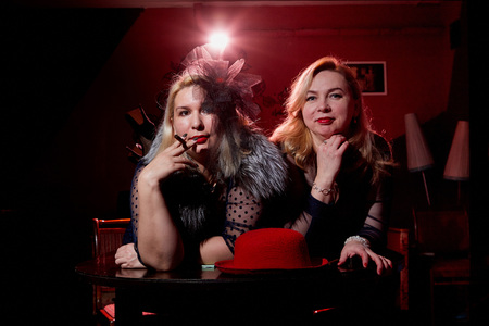 Two fat women in a dark room with red light. Gangsters style