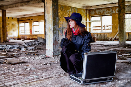 Girl in a black cloak and hat with a diplomat in a ruined room. A spy in a secret meeting. Unusual photoshoot