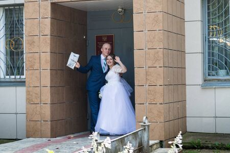 Kirov, Russia - July 27, 2018: Bride and groom near registry office before marriage registration in a summer day