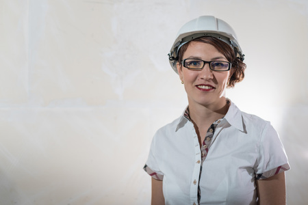 Cute nice young woman in white construction protection building helmet and unfinished apartment in the background. Female architect, desigher or engineer. New resident in an unfinished room 免版税图像