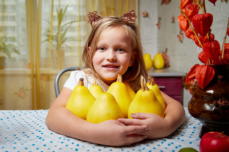 A little girl sitting at a table with yellow zucchini