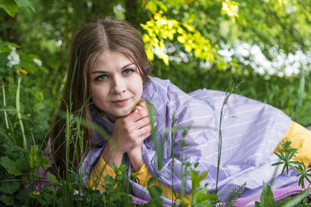 Beautiful young woman on the grass in the park at a summer or a spring time Фото со стока