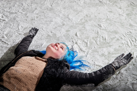 Girl with blut hair lying on the snow of a ice arena on the city square in winter evening Stock Photo