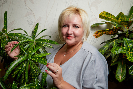 Plump blond woman near green plants in the room Stock Photo