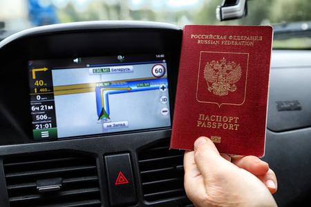 Russian passports and car Navigator in the background. Concept of travel abroad by car for Russian citizens