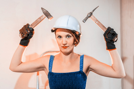 Sexy cute girl who is builder, painter, worker being in a renovated room. Two hammers in the hands of a woman