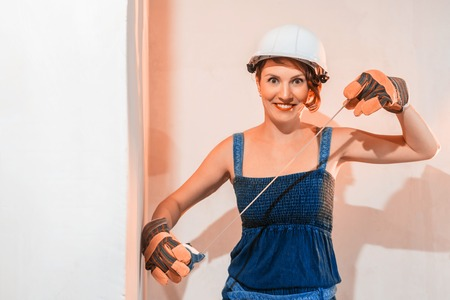 Sexy cute girl who is builder, painter, worker being in a renovated room. Construction roulette in hands of woman