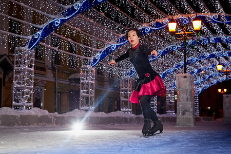 Girl skating on the ice arena in the evening city square in winter evening 免版税图像