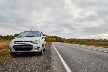 Car on the road and landscape with field and sky in an summer on an autumn day