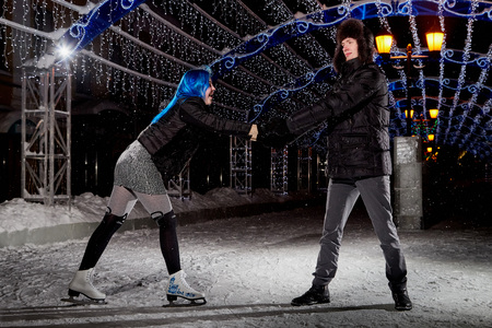 Couple on the city rink in a winter evening