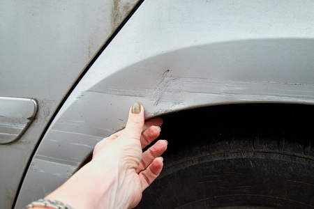 Female hand showing the scratches on the damaged car of silver color. Concept of accident and insurance Banco de Imagens