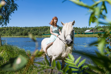 Young girl and white horse near lake in summer sunny day