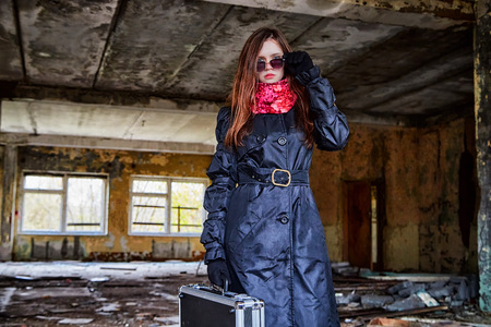 Girl in a black cloak with a diplomat in a ruined room. A spy in a secret meeting. Unusual photoshoot