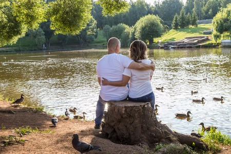 Adult couple loving each other in the Park on a Sunny summer day. Ordinary family consisting full man and full woman hug each other Stock Photo