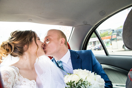 Russian bride and groom inside of the car Imagens