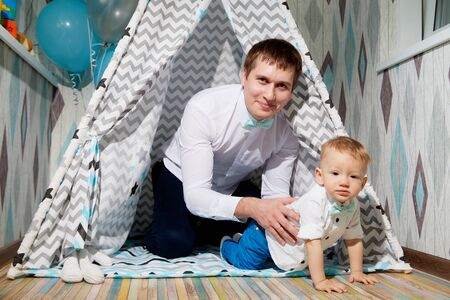 Small male child with fater on the floor in wigwam or teepee during a photo shoot in the room in 1 year