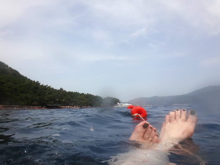 Sea surface with buoys, woman legs under water and mountains in the distance. View and shooting from water in a summer day