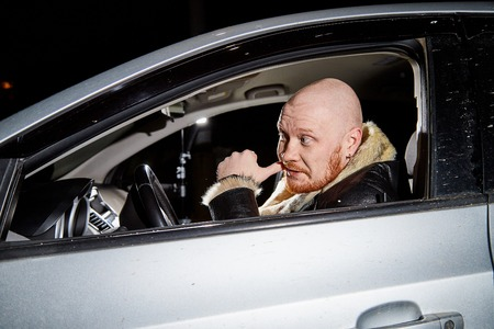 Male driver in a leather jacket smoking in the car in the dark time. Drunk driver in the car. Night unusual photo shoot.