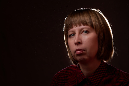 Portrait of ugly but sweet girl with chubby cheeks and black background Imagens