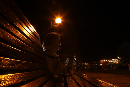 Girl at night at the bench in the city Park with lanterns. Taking pictures in a dark key
