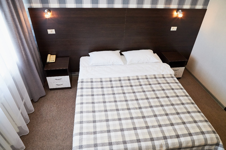 Bed with white linen and plaid pattern blanket in the room with two lamps
