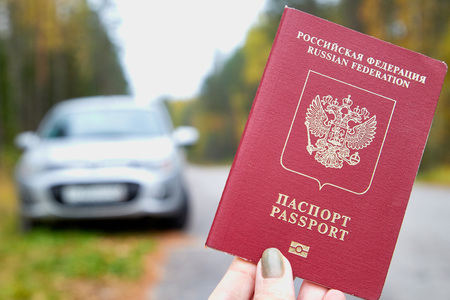 Russian passport in the hand of woman and blur car background. Concept of travel abroad by car for Russian citizens Zdjęcie Seryjne