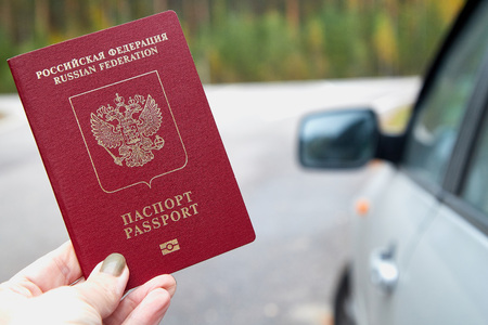 Russian passport in the hand of woman and blur car background. Concept of travel abroad by car for Russian citizens