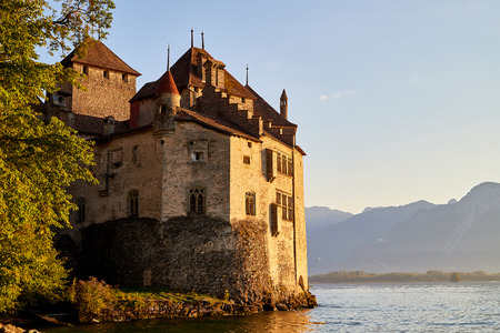 Beautiful castle standing in the water of the lake and mountains in the background with sunset. Chillon Castle, Switzerland near Montreaux and Lake Geneve
