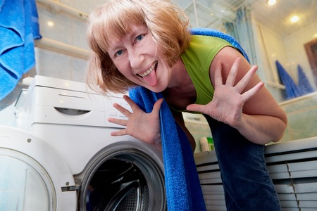 Housewife near washing machine doing selfie in the bath room. The concept of homework and Laundry at home