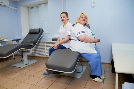 Erfahrene dicke Frau des Arztes und aufstrebende junge Ärztin sitzt auf der medizinischen Couch im Krankenhaus in Russland Standard-Bild