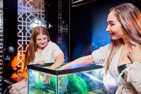 Young women in beauty salon. Fish pedicure and manicure in new modern spa treatment with beautiful with color light