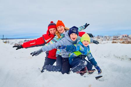 Porträt einer Familie mit vier Leuten, die Spaß im Schnee haben Standard-Bild