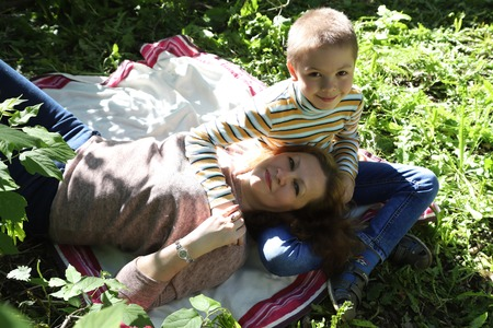 Mom and son having fun in the park in a summer sunny day