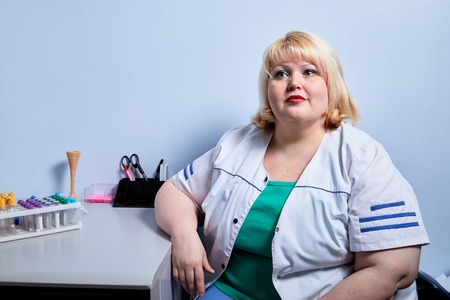 Portrait of experienced doctor fat woman in medical office at the hospital in Russia
