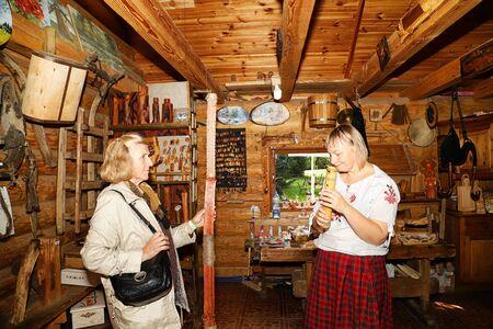 Dudutki, Belarus - September 13, 2018: Guide telling tourists in manor Dudutki about the national craft in Belarus. Folk musical instrument