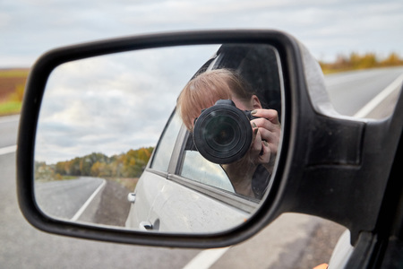 Car mirror, the reflection of the female photographer in it and landscape with field and tree in a summer or in autumn day