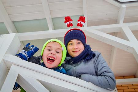 Two cute boys dressed in coats have fun on a winter walk near house Фото со стока