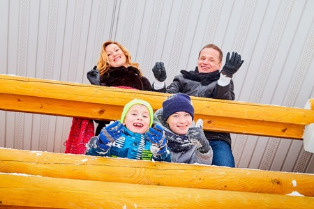 Portrait of a family with four people having fun near wooden village house. Dad, mom and two sons in winter day outdoor