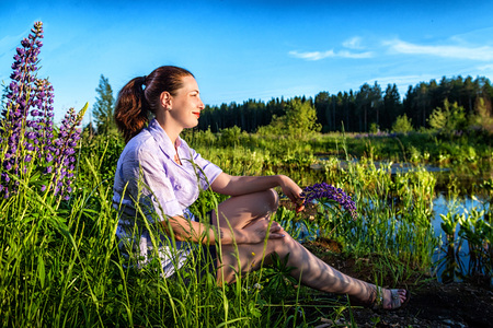 Portrait of a nice woman near water in a summer sunny evening