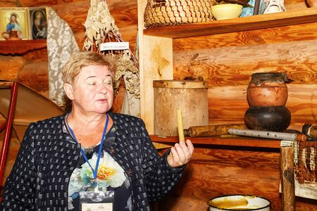 Dudutki, Belarus - September 13, 2018: Guide telling tourists in manor Dudutki about the national craft in Belarus