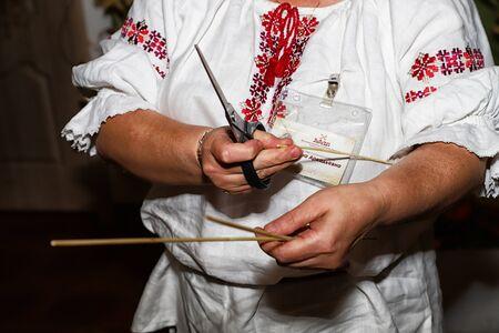 Dudutki, Belarus - September 13, 2018: Guide telling tourists in manor Dudutki about the national craft in Belarus. Folk weaving of straw