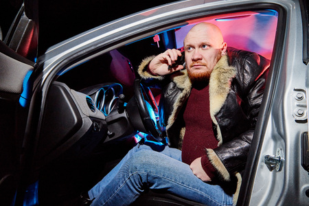Male driver in a leather jacket in the car in the dark. Night unusual photo shoot