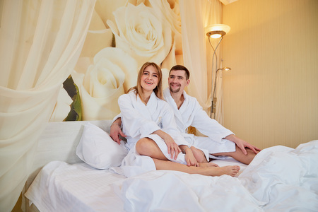 Couple of tourists resting in beautiful hotel room on vacations. Honemoon travelers in white bathrobe in the wedding room Stock Photo