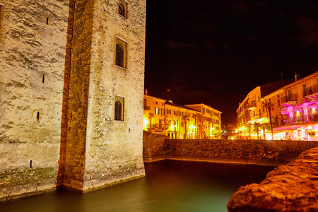 Big stone castle in Sirmione in Italy on a summer night and beautiful light. City night landscape
