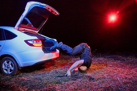 Guy jumpint from the trunk of a car in a night time and colored red and blue light around. Photoshoot about life of gungsters in Russia