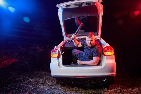 Guy with an axe in the trunk of a car in a night time and colored red and blue light around