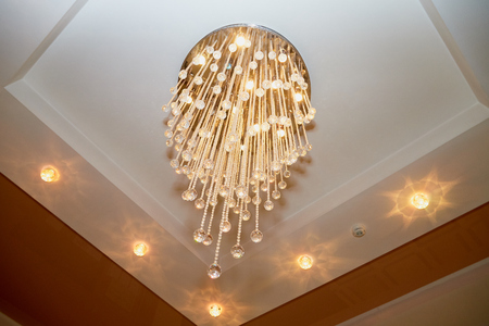 Modern chandelier with shiny crystals on white ceiling